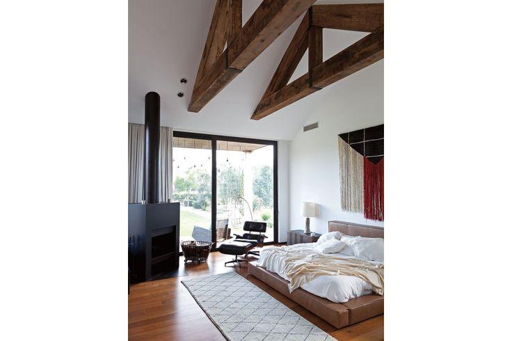 Una casa decorada con madera y cemento  Karina diseñó una cama baja tapizada en cuero, y la acompañó con un cajón de madera como mesa de luz (Pablo Ledesma), un gran tapiz artesanal (Guayruro), un sofá de lectura Eames que los propiestarios trajeron de su casa anterior y una alfombra con motivos geométricos (Restoration Hardware) Foto:Living/Magalí Saberian