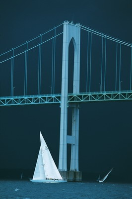 The 12-meter class sloop Columbia races under the Newport Bridge during the annual Museum of Yachting Classic Regatta in Newport, RI. The black sky hints of the pending squall that hit Newport after the last boat finished. Canon EOS 1v, 300mm lens, Fuji Velvia