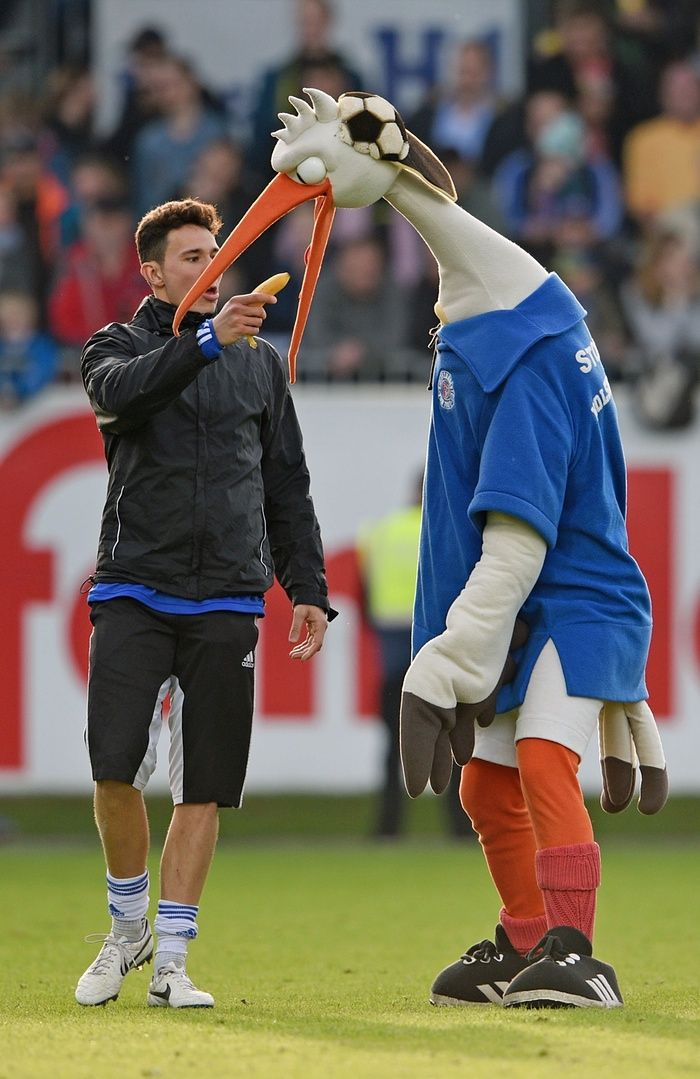Kiel's Niklas Jakusch plays around with mascot Stolle during half-time of the third division match between Holstein Kiel and Arminia Bielefeld