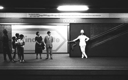 """A Municipal Police agent, commonly known as """"ghisa"""" in Milan, at Duomo station. Picture by Carlo Orsi, 1964. The line 1 map was already showing the South-Western branch towards Gambara, which was already under construction but not opened yet."""