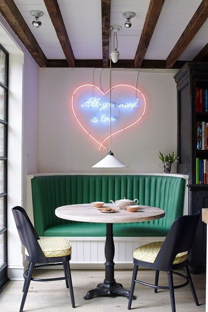 Small Round Dining Table Curved Green Banquette Seating booth, modern dining chairs and a Tracey Emin neon spelling 'All You Need Is Love' on the wall. Small Space Ideas.s.