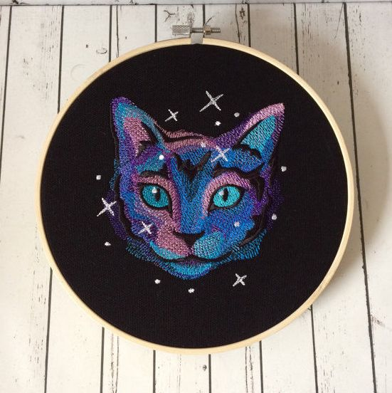 """A beautiful cat, machine embroidered on black canvas, in an array of galaxy colours. It is framed in an 8"""" wooden hoop and has a ribbon to hang it on the wall. The back is neatly finished with cream f"""