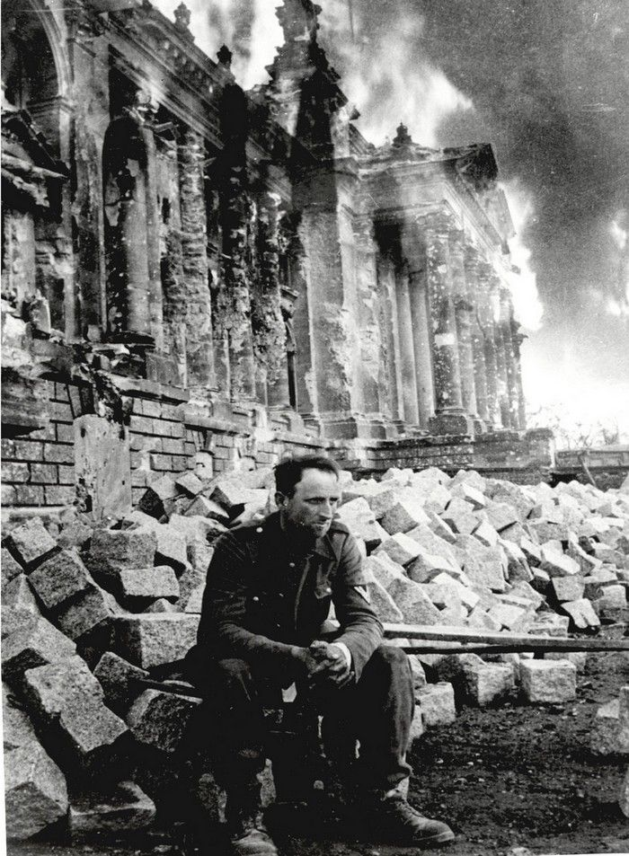 Defeated German soldier in front of burning Reichstag, Berlin, 1945 - Mark Redkin