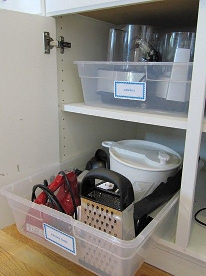 """Putting like items together in storage bins can help keep deep cupboards organized, and make it much easier to find what you're looking for. Simply find the appropriate bin (like """"small appliances""""), pull it out, and remove what you want! No more digging and stretching."""