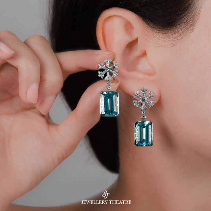 Jewellery Theatre.  New earrings are made from 18K white gold and feature 2 emerald cut aquamarines cut aquamarines at 17.41ct complemented by 348 diamonds and 4 aqua diamonds. #jewellerytheatre #diamondearrings #snowflake