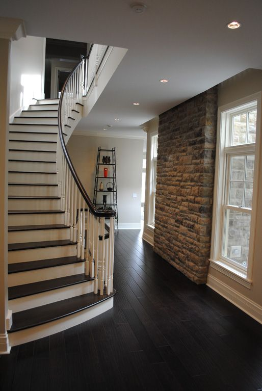 COOK ARCHITECTURAL Design Studio│City home showcases a curved stair case with dark wood floors and a dark handrail which complements the white balusters and painted risers.