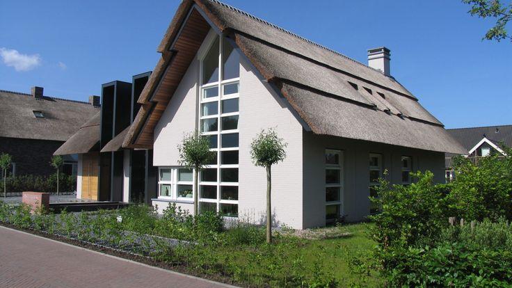 modern landelijke woning | vrijstaande witte villa met kenmerken van een boerderij, een getrapte rieten kap, karakteristieke gebouwhoge kaders en strakke witte kozijnen