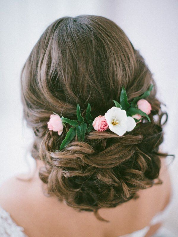 long wavy low updo hairstyle for wedding with pink flowers / http://www.deerpearlflowers.com/wedding-bridal-hairstyles-for-long-hair/