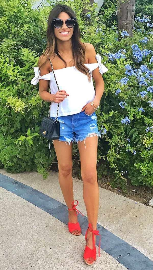 Look de verão, com blusa ombro a ombro branca, shorts jeans rasgado e sandálias vermelhas.
