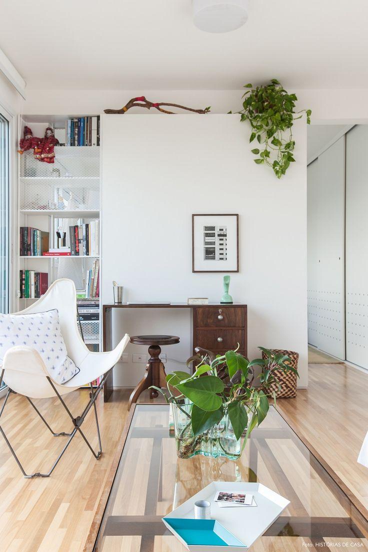 Sala de estar minimalista com poltrona butterfly, mesa de centro de madeira e escrivaninha vintage.
