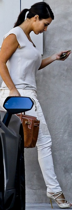 Who made  Kim Kardashian's white sandals, white skinny jeans and tan suede handbag that she wore in West Hollywood?