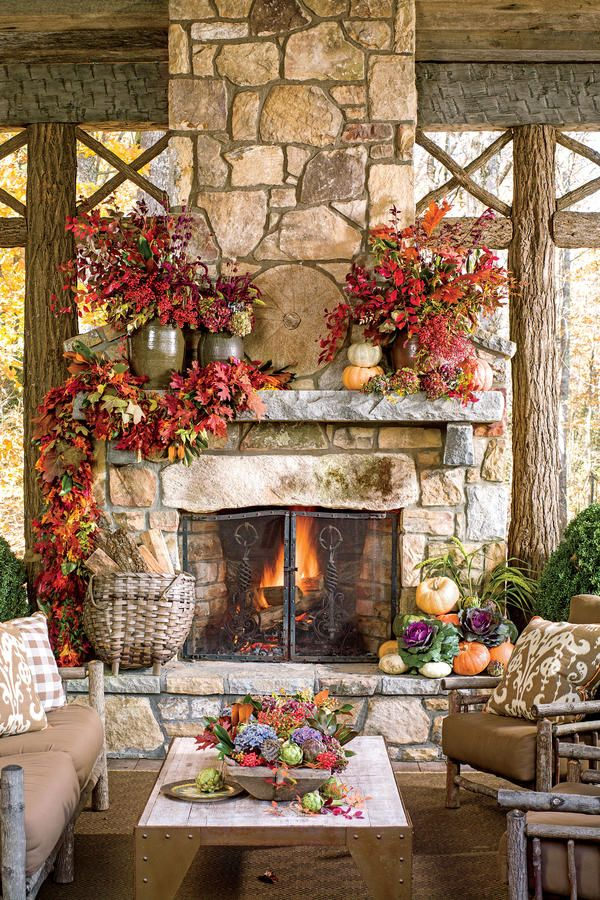 Cozy Outdoor Fireplace - Fall's Best Outdoor Spaces - Southernliving. Create a festiveretreat for guests with lots of plush seating and a mantel swathed in a foliage garland made from a combination of oak and magnolia leaves. Swag only one side of the fireplace for a modern feel.Complete the look withsimple and weighty pottery crocks filled with autumn leaves, hydrangeas, and berries.     Tip: Dry your summertime hydrangeas to use in fall arrangements.