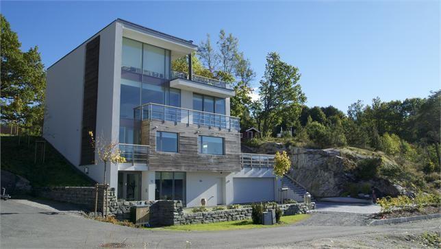 Dette er et hus bygget for et vakkert utsyn som kan være både fjell, skog og vann eller flunkende lys fra en storby. Huset plasseres fint på skrånende tomt. Funkishus - murhus - pusset fasade - Leca