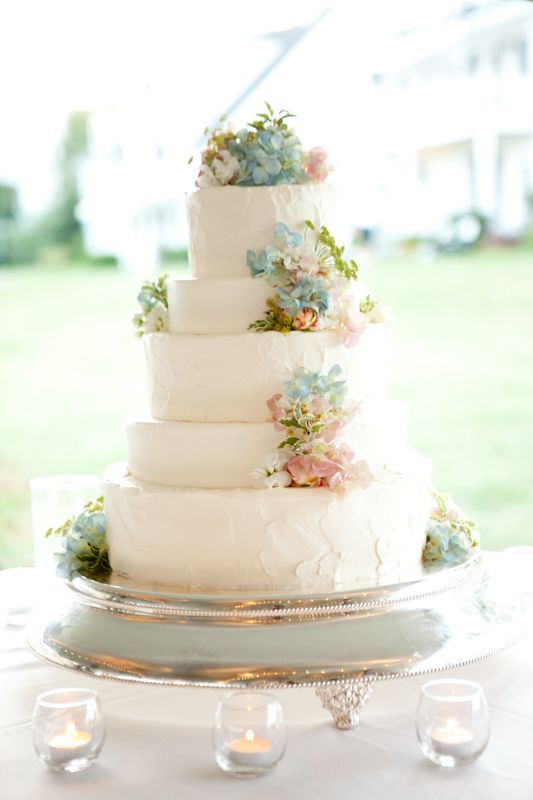 The cake will have simple, small scattered clusters of light blue hydrangeas, lavender spray roses, peachy pink spray roses, and pale yellow spray roses on top and on the tiers.