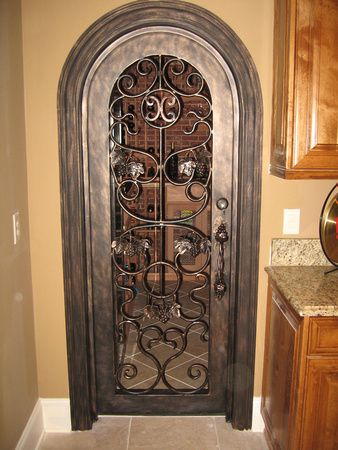 Lovely scrollwork on this door to a wine room.