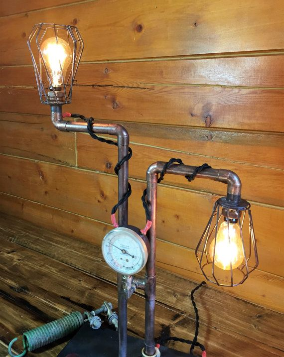 "This tall steampunk lamp is made of copper pipe, and has a beautiful aged patina. It has been fitted with a 4 inch gauge, vintage cloth covered twisted-wire and is controlled by the switch mounted on the base. The two amber Edison bulbs give off a nice warm light. (bulbs included).  The lamp is mounted on a 12"" by 6"" wooden base and stands 24"" tall."