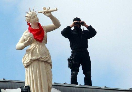 Un ufficiale di polizia francese controlla i festeggiamenti attraverso un binocolo sul tetto del municipio, all'apertura della notte della festa Bayonne, o