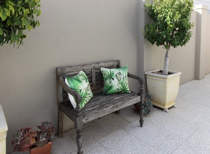 Outdoor timber bench with palm leaf cushions.