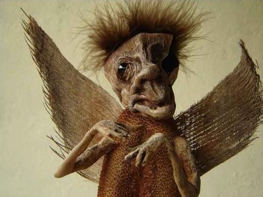 """""""Del cielo provienen todo tipo de criaturas, y no todas son como las pintan.""""  Extraño ángel - Carlos Miller / Técnicas mixtas sobre coco deshidratado, semilla de lengua de vaca, incrustación de esféra de agata negra y tejido de palmera. Formato 35x20x10 cms."""