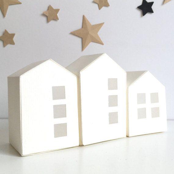 Créez une ambiance lumineuse, originale, grâce à ces 3 photophores en forme de maison, confectionnées, à la main, avec du papier de haute qualité, de coloris blanc.  De jour, comme de nuit, elles ajoutent une touche intemporelle à votre décoration. Dès la tombée de la nuit, elles s'illumineront grâce à des bougies LED (non fournies) que vous glisserez à l'intérieur.  Les maisons sont réalisées avec du papier blanc , qui laisse passer une douce lumière à travers les fenêtres. Elles sont de 3…