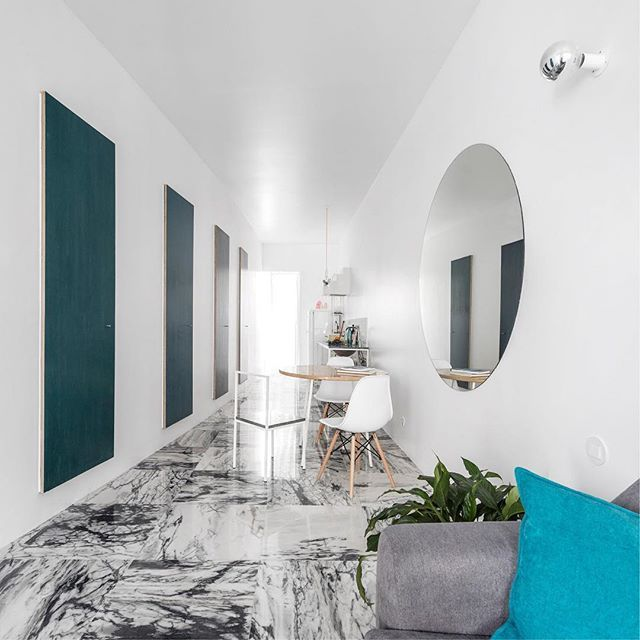 Porto architecture studio Fala Atelier has overhauled a fragmented 19th-century Lisbon flat, creating a long narrow living area framed by a subtly curved wall. Find out more on dezeen.com/interiors #interiors #interiordesign #Lisbon #apartment Photograph by Fernando Guerra.