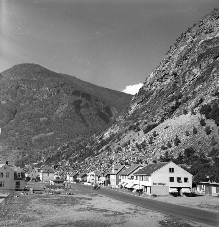 DigitaltMuseum - torget, Øvre Årdal, 28.08.1955, oversiktsbilde, fjell i bakgrunnen.