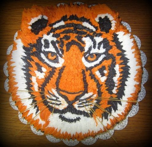 """LSU Mike the Tiger - Inspired by lalaine's white tiger cake.  This is a 10"""" x 3"""" WASC cake piped with buttercream.  Whiskers are angel hair pasta.  Ears are cookies (pecan sandies) covered in BC. Mostly used tip 21...but used smaller star tips to get in the narrow areas.  The tip of the nose and eyeballs was done using a 4 tip."""