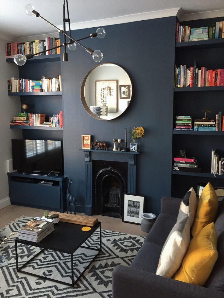Dark blue living room. Styled dark using Farrow & Ball's Stiffkey Blue, accessorised with warm yellow accents. #farrowandball #stiffkeyblue #styleitdark #darkwalls #darkpaint #livingroomdesign #interiordesign #myhomevibe #londoninteriordesign #bookshelf #shelfstyling #blue #roundmirror #fireplace