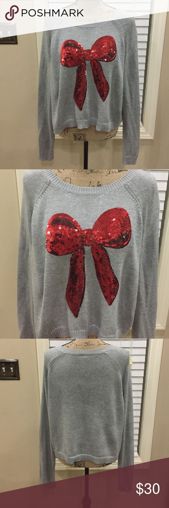 "Boutique grey sweater with sequined bow front Boutique grey sweater with sequined bow front-wildfox style! Super cute and soft-cropped look. Preloved in excellent condition. Oversized fit. Pit to pit measurement is 24"". Length 22"". So fun! 55% cotton 45% polyester-very soft and cozy. boutique Sweaters Crew & Scoop Necks"