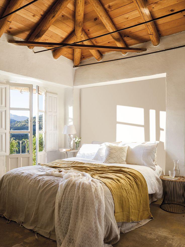 00437076. Dormitorio principal completamente blanco con vigas de madera y un plaid mostaza