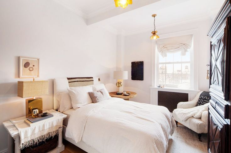 A cozy bedroom with white bedding, a large brown cabinet, and a marble night stand