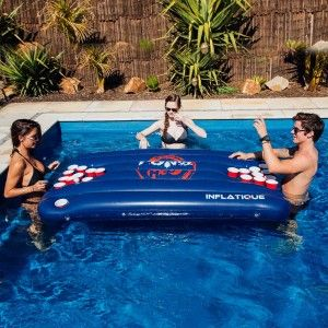 Floating blue inflatable beer pong table in swimming pool