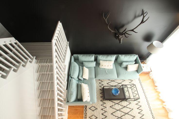Chalet rustique chic, tête de chevreuil, sectionnel bleu poudre, mur noir, mur de rideaux