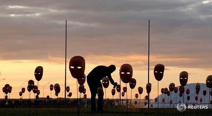 A man paints masks during a protest by non-governmental organization (NGO) Rio de Paz (Rio of Peace) against political corruption scandals, in front of the National Congress in Brasilia, Brazil May 23, 2017. REUTERS/Paulo Whitaker #reutersphotos #reuters #brazil #rio #masks #silhouette