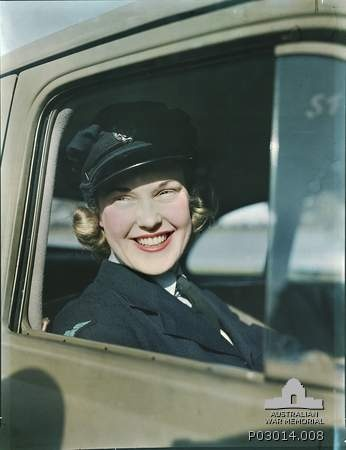 An unidentified female driver in the Womens Royal Australian Air Force (WAAAF), smiles as she looks out from the open window of her car. c 1941.