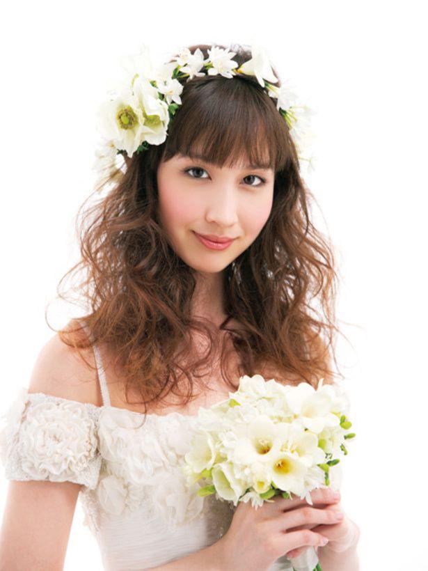 ゆるいカールのダウンヘアと白花でピュアな魅力満載。大きい花ばかりだといきすぎになってしまうので、小花を軸にし、片側だけに大ぶりの花をアクセン...