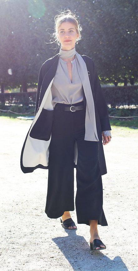 Sophie Buhai in a silk v-neck blouse, black wide-leg pants and black slides with a light jacket