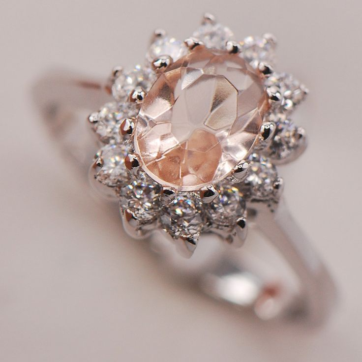 Featuring a Morganite stone with a halo of cubic zirconia stones, this sterling silver ring beams with feminine beauty. Ring Details: - Metal: sterling silver Stone Details: - Stone type: morganite, c