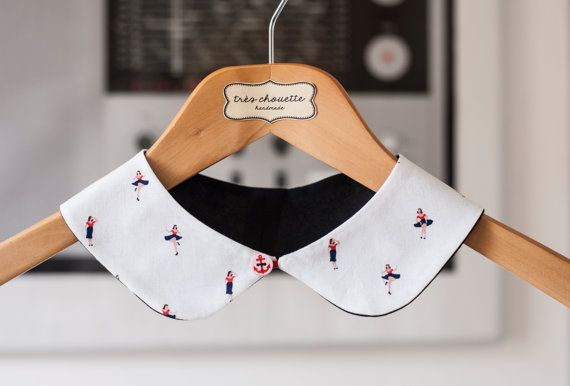 White rounded Peter Pan collar featuring small pinups. With red a maritime button closure on the front.