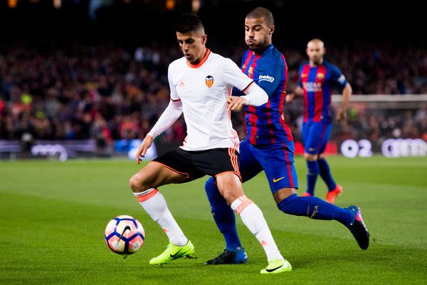 Joao Cancelo (L) of Valencia CF protects the ball from Rafinha of FC Barcelona during the La Liga match between FC Barcelona and Valencia CF at Camp Nou stadium on March 19, 2017 in Barcelona, Catalonia.