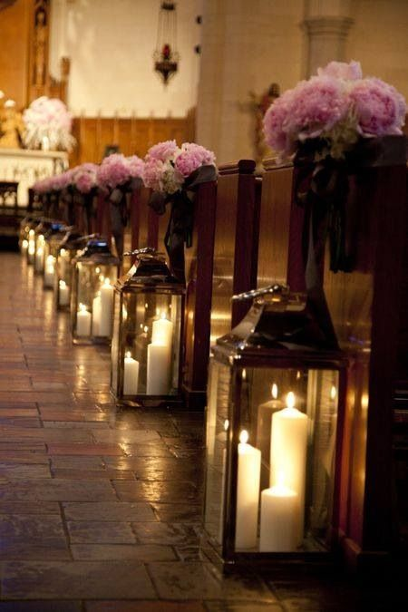 Romantic glow in the church. I love this look, candles in glass lanterns and flower bouquets on the end of the isles. This is so romantic!