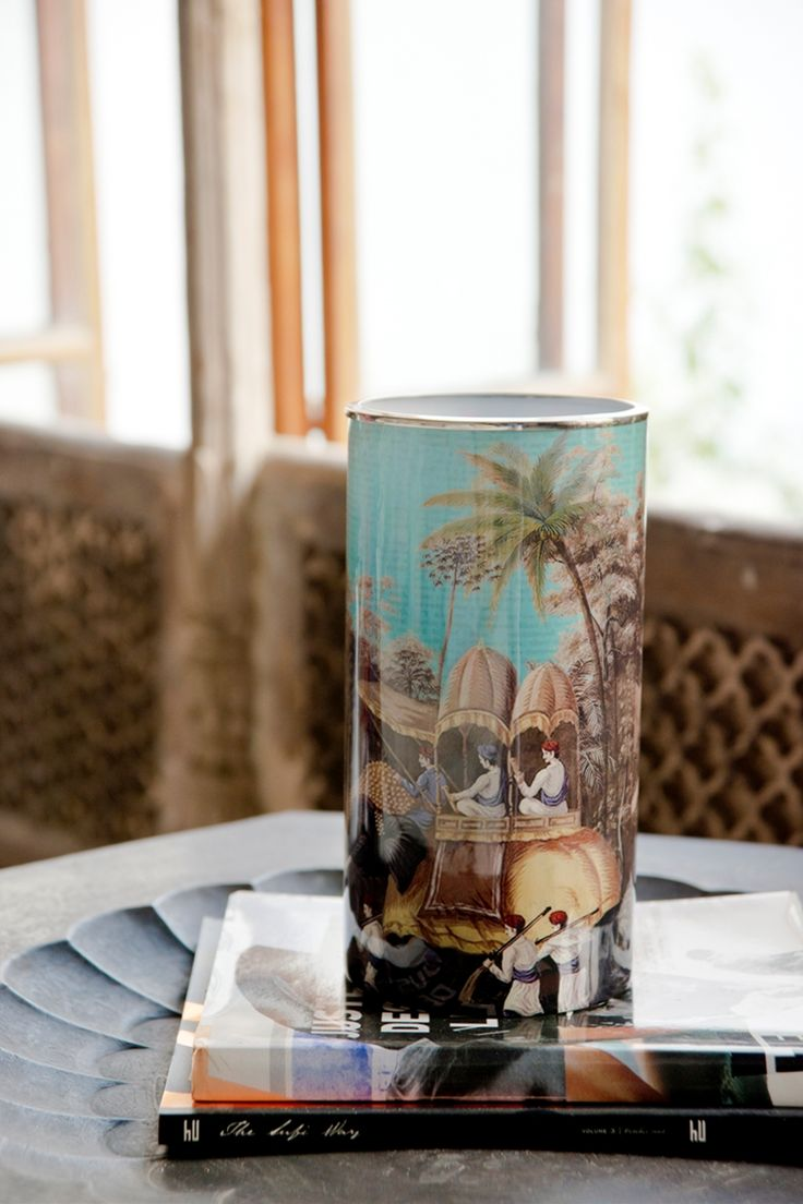 GOLDEN HOWDAH DECOR VASE glass vase decorated with tropical motifs and a shiny nickel rim. Can be used to hold a candle or even a small posy on a centre table.