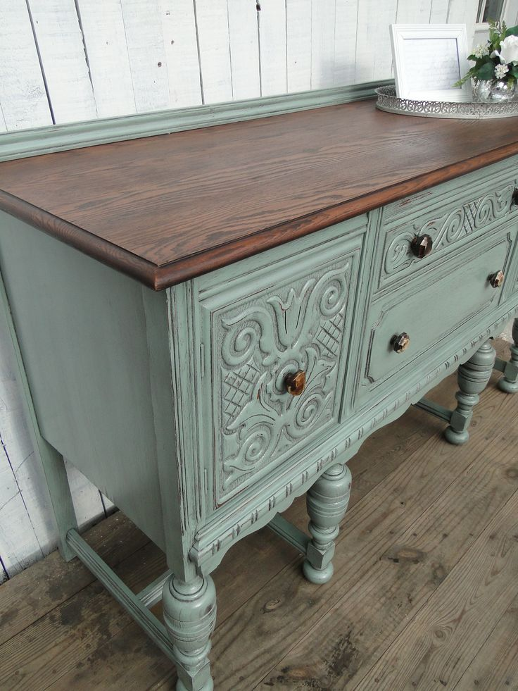 Ornate oak buffet in a light springtime green, dark natural top, new knobs give it an organic look and feel. Modern Vintage