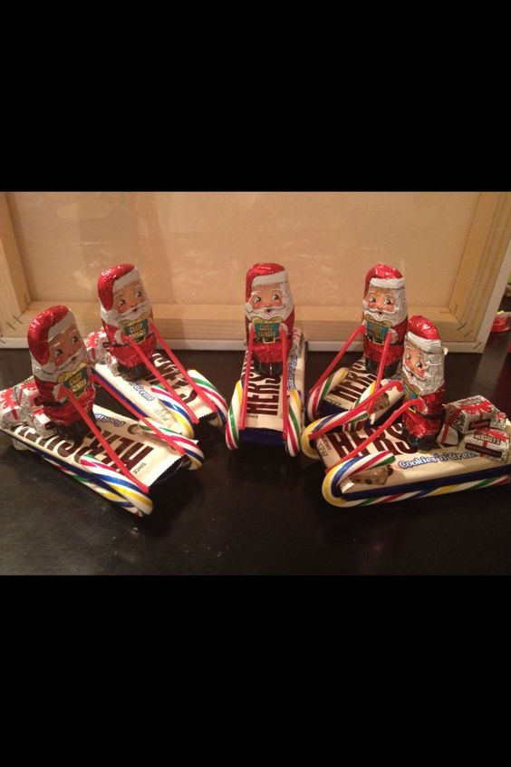 Large candy bars and candy canes for sleigh. Chocolate Santas holding Twizzler pull n peel ropes. Chocolate gifts.
