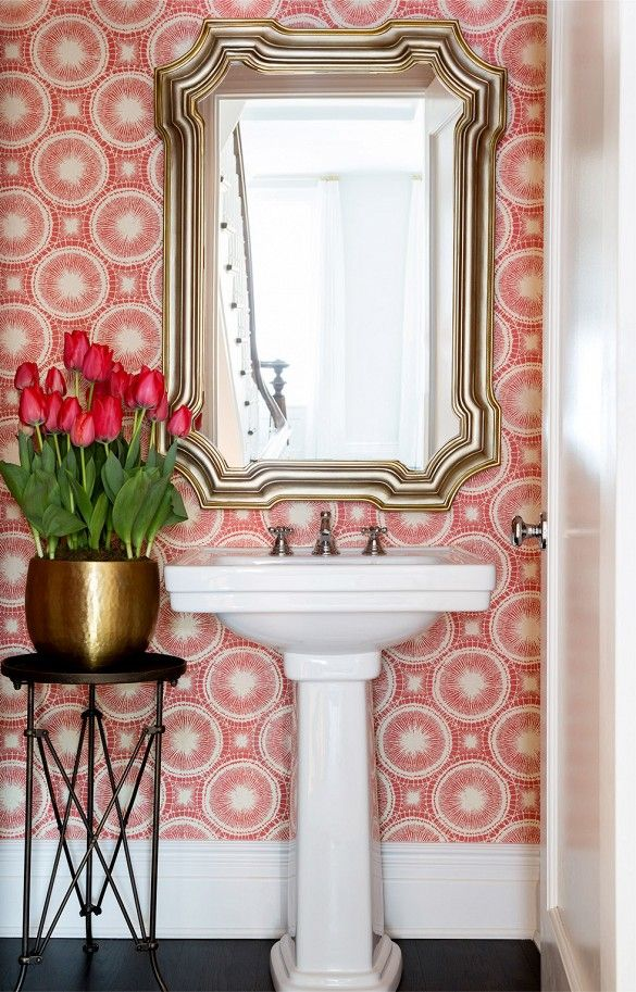 Bright patterned wallpaper with metal side table, pendant sink, and large gold mirror.