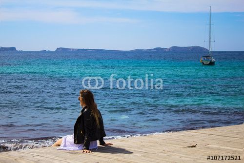 Young woman sitting on the pier with stunning view  of the sea and island