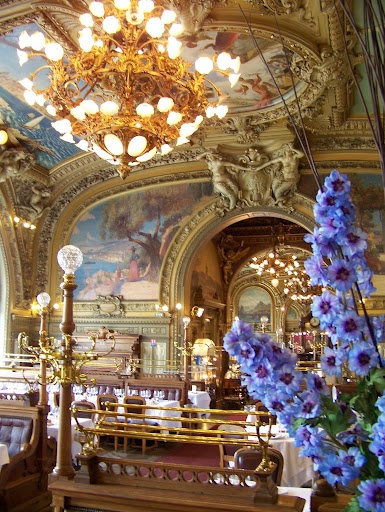 """Paris-Lyon-Mediterranean (PLM) Company built the restaurant for the  1900 Exhibition. It was renamed """"Le Train Bleu"""" in 1963 to celebrate the """"Paris-Vintimiglia"""" line & granted historical monument status in 1972.  It's famous for the forty-one paintings, including landscapes traveled through by the PLM trains, waxed parquet flooring, wood panelling, and long, leather-upholstered wall-seats. Regulars have included Coco Chanel, Brigitte Bardot, Salvador Dali and Jean Gabin. [3rd of three pins]"""