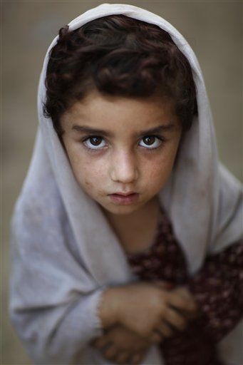 Girl poses for a photo in an Afghan refugee camp on the outskirts of Islamabad, Pakistan. (AP Photo/Alexandre Meneghini)
