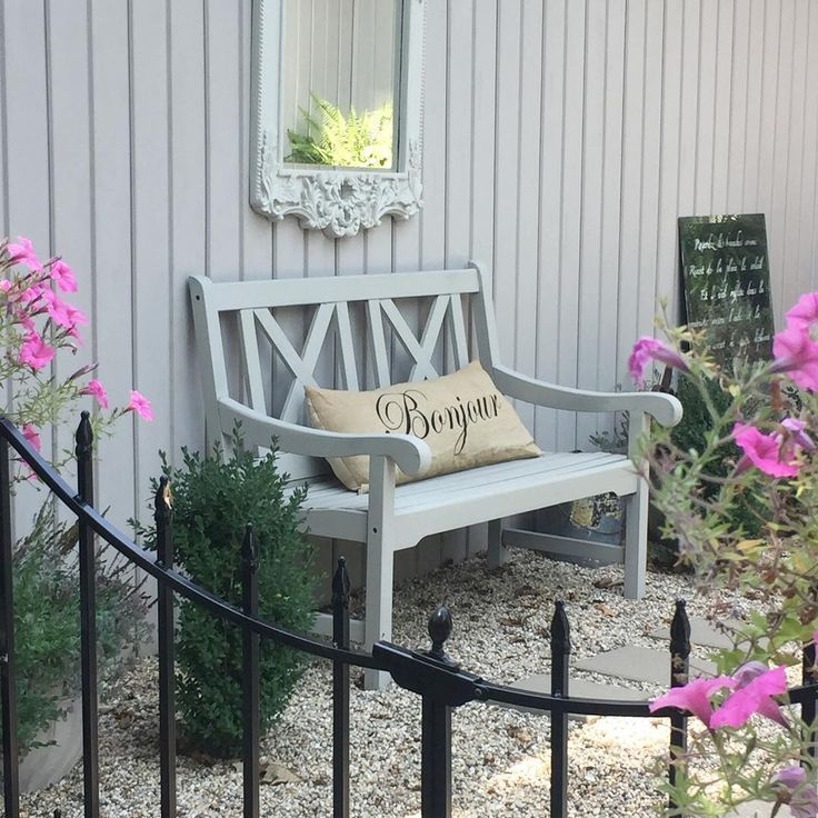 French courtyard with bench, pea gravel, and pink flowers - Hello Lovely Studio.