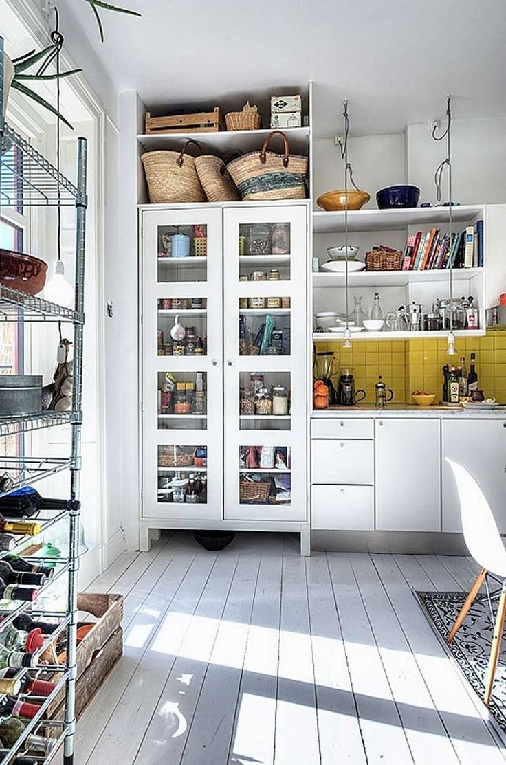 Even if you're not a fan of the open shelving look, there are a few great ideas in this Scandinavian kitchen: a nook above the semi-see-through pantry closet for shopping baskets, suspended lights over the countertop, a yellow tile (!) backsplash that wraps around the wall. See more photos below:
